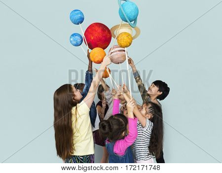 Diverse group of kids holding planets on sticks isolated background