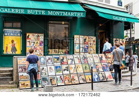 Paris France - June 28 2016: The charming quarter of Montmartre hill with traditional french cafes and art galleries. Old art prints for sale in Montmartre gallery. Tourists are looking at paintings displayed for sale.