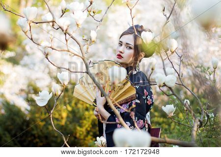 Geisha walking in the garden with magnolias. Soft and colors