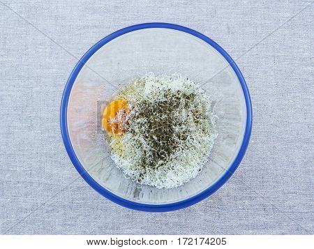 Raw egg grated white cheese and spices in a glass bowl with a blue border on a background of a linen tablecloth. View from above.