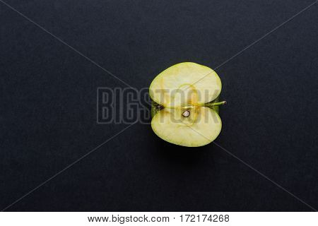 longitudinal cut or section of one apple as the isolated object closeup on black or against a dark background