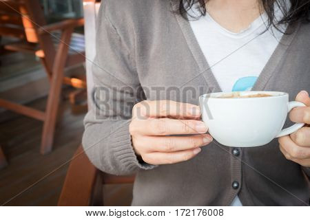 Woman's hand holding a cup of redolent cappuccino coffee.