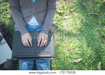Laptop on the lap of a woman sitting on the lawn.