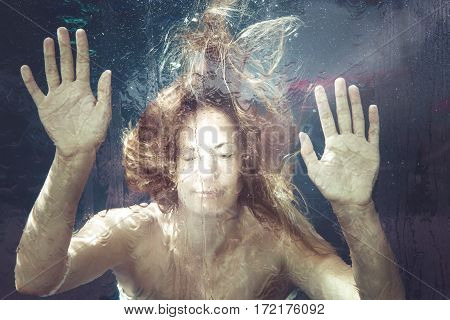 Woman under water. A young woman is trapped in a water surface. Hands resting on. summer feeling.