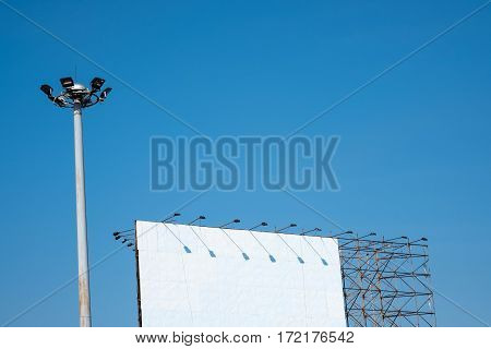 Lamp post and billboard with blue sky background.