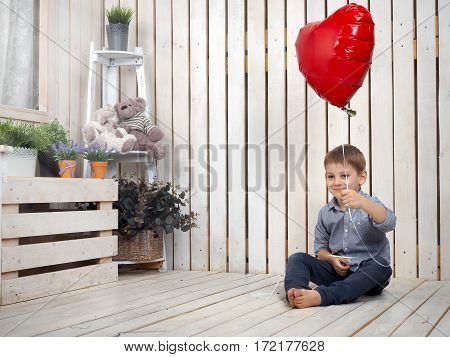 Little happy boy with a red balloon in the shape of a heart. Children's room in a retro style. Toys flowers
