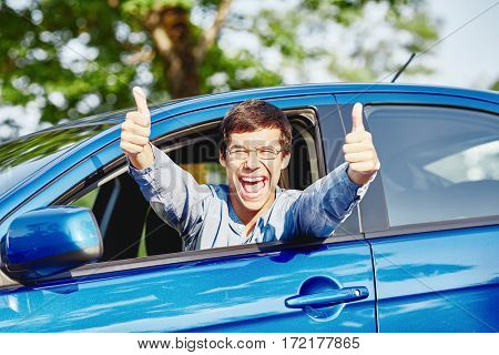 Close up of young hispanic man wearing glasses showing thumb up hand gesture with both hands and happy screaming through car window - new drivers concept