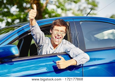 Close up of young hispanic man wearing glasses showing thumb up hand gesture and happy screaming through car window - driving school and new drivers concept