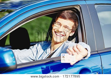 Young hispanic man wearing glasses and jeans shirt sitting behind wheel and holding out his driving license through car window - new drivers concept