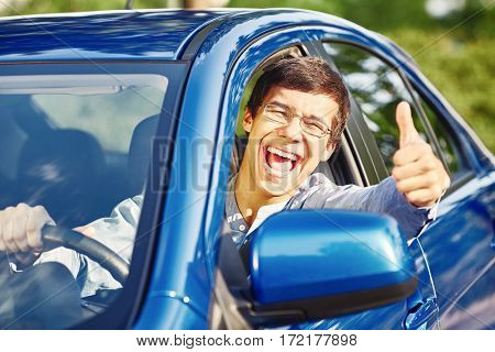 Young happy hispanic man wearing glasses sitting inside car, holding steering wheel, showing thumb up hand gesture through car window and laughing - driving school and new drivers concept
