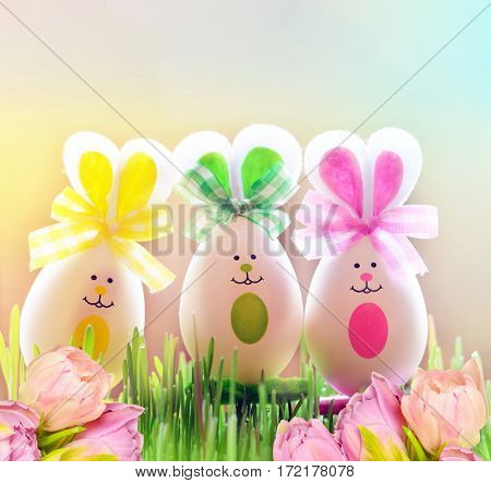 Colored easter egg bunnies on green grass and flowers.
