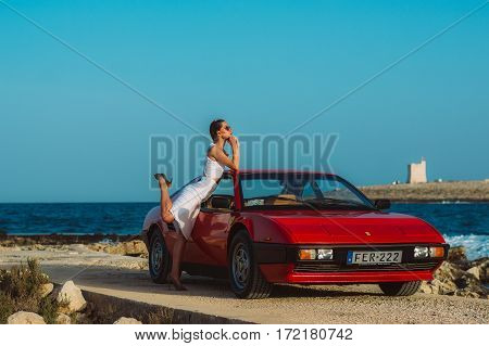 Young Beautiful Girl In Sunglasses Posing Near The Red Ferrari