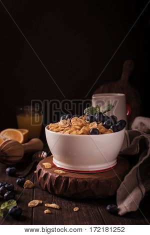 Healthy breakfast with corn flakes, berries and milk on old dark wooden background. Copy space. Retro style toned.