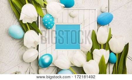 Easter decoration with tulips and frame on wooden background