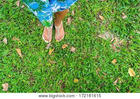Female Foot In Sandals On A Green Grass