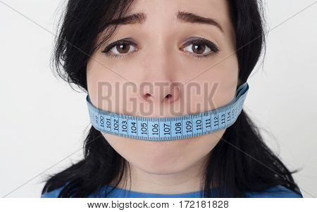 Diet, weight loss and stress concept. Closeup portrait of young sad woman with a blue measuring tape around her mouth on white background.