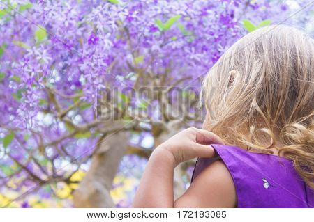 Little Girl On The Background Of Purple Wood