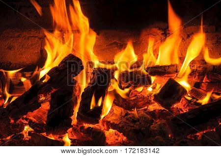 Glowing Log in a Dying Fire. bright flames burning wood on black background