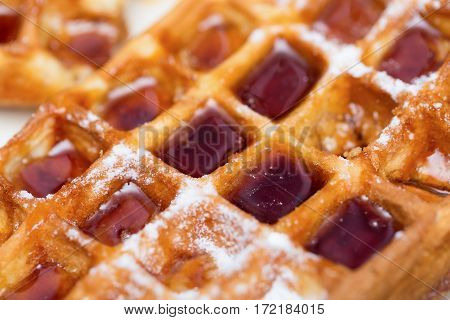 Whole wheat Belgium waffle with maple syrup close up as background.