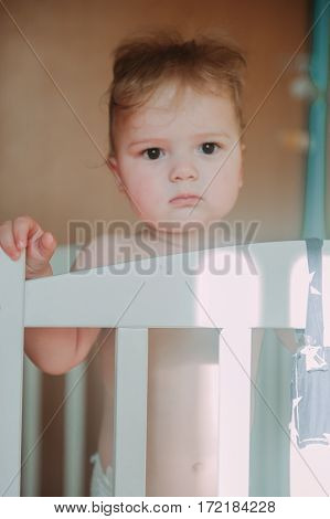 Baby blonde boy 1 year old sitting in the crib