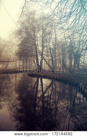 Walkway at the canal in morning mist.