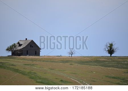 Lone abandoned and vintage home on the open windswept prairie grassland in the dry summertime heat