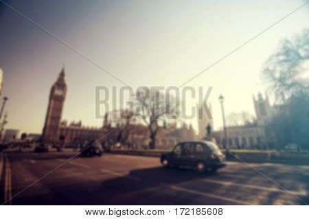 Big Ben in Westminster with red London Buses and traffic. Blurred background.