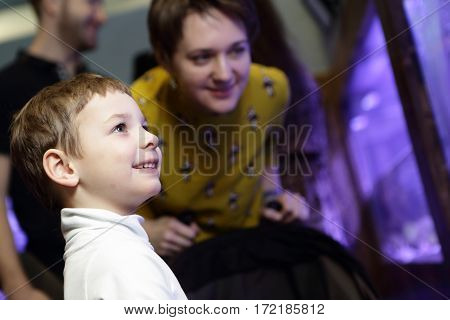 Mother with her son looking at aquarium at amusement center