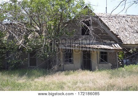 Abandoned and weathered old wooden house with overgrown yard