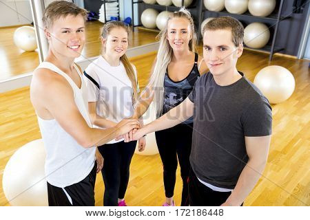 Happy and smiling fitness workout group holding hands at the gym center. Teamwork and motivation.