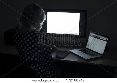 Overtime in the office. A young woman working at the computer late at night