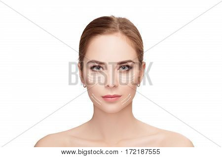 Spa portrait of attractive woman with arrows on her face over white background. Face lifting concept. skin care