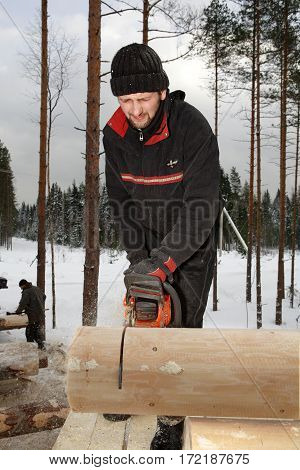 Leningrad Region Russia - February 2 2010: Builder trims a log with a chainsaw the sawdust flying.