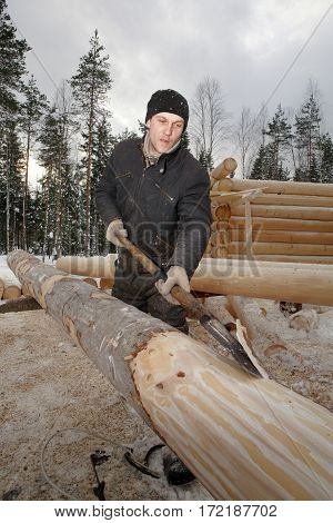 Leningrad Region Russia - February 2 2010: The process of peeling and debarking of wood Worker hand peeled logs for log cabin construction.