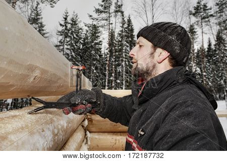 Leningrad Region Russia - February 2 2010: Woodworker makes marks on a log surface using scriber tool equipped with two levels it transforms the contours of the lower log to the upper one.