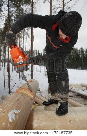 Leningrad Region Russia - February 2 2010: Building the log walls cutting round saddle notch using chainsaw.