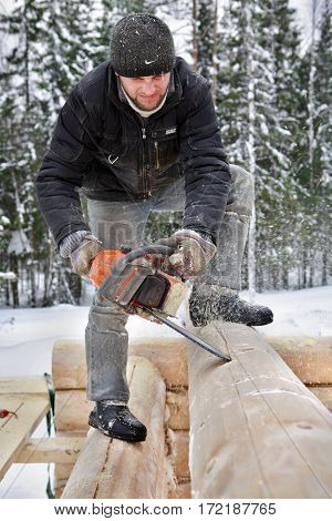 Leningrad Region Russia - February 2 2010: Log house building build a log house following the lateral lines with the chain saw creates a v- shaped cutout to house the lower log on the wall.