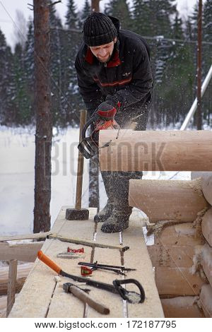 Leningrad Region Russia - February 2 2010: Construction of wooden log cabins makes the notch on the end of the log using a chainsaw.