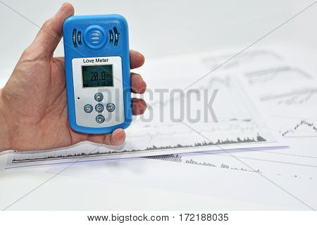Mans hand with Love meter. Abstract photo with documents.