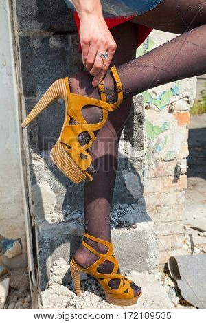 Woman's hand fastening a buckle of the high heel sandals. Close-up.