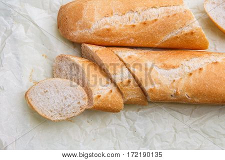 Hot french bread on wax paper at wooden table
