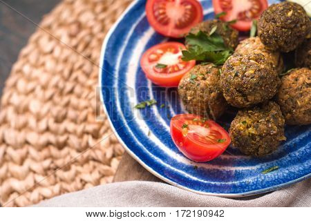 Falafel with tomato and celery on a blue plate on a wicker napkin horizontal