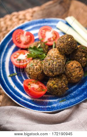 Falafel with tomato and celery on a blue plate vertical