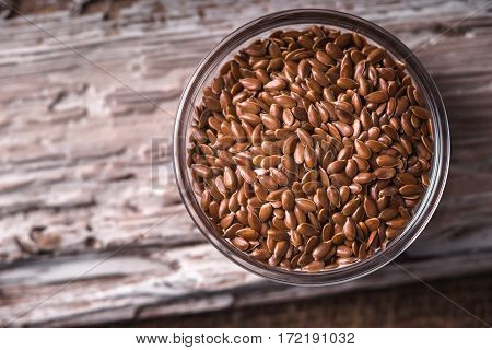 Linen seeds in a glass bowl on wooden stand closeup horizontal