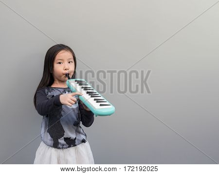 Little Asian Child Play The Melodion, Gray Background
