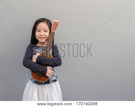 Little Asian Child Play The Ukulele, Gray Background