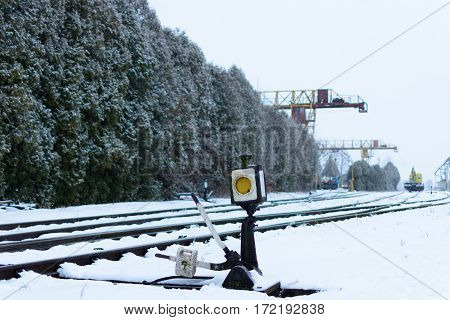 Rail switch (Hand rail shooter) in the snow. Railway.  In the background gantry cranes.