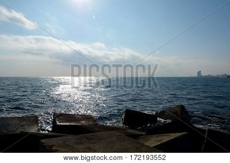 Concrete blocks on sea shore in Barcelona Spain. Sun reflections in water. Distant boats and buildings visible.