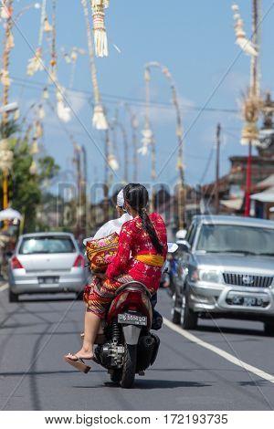 Bali, Indonesia - September 7, 2016: Balinese family on riding motorbike on streets of Ubud during Galungan celebration.