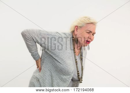 Senior woman having backache isolated. Lady touching her back. How to cure lumbago.